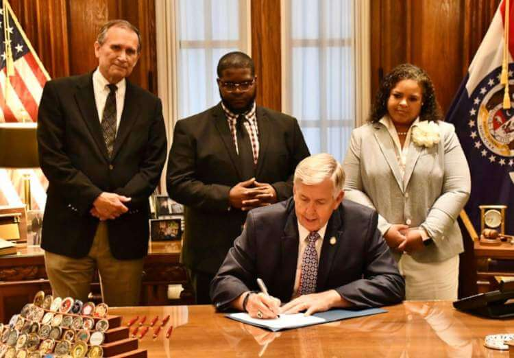 Photo of Governor Michael Parson signing SB203. Also pictures Paul M. Brown; Jason Groce, Chief of Staff for Senator Jamilah Nasheed (St. Louis); and Senator Nikki Curls (Kansas City)